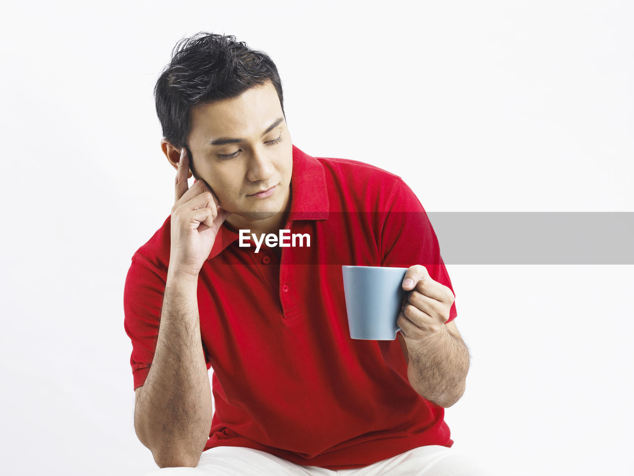 Young Man Holding Coffee Cup Against White Background