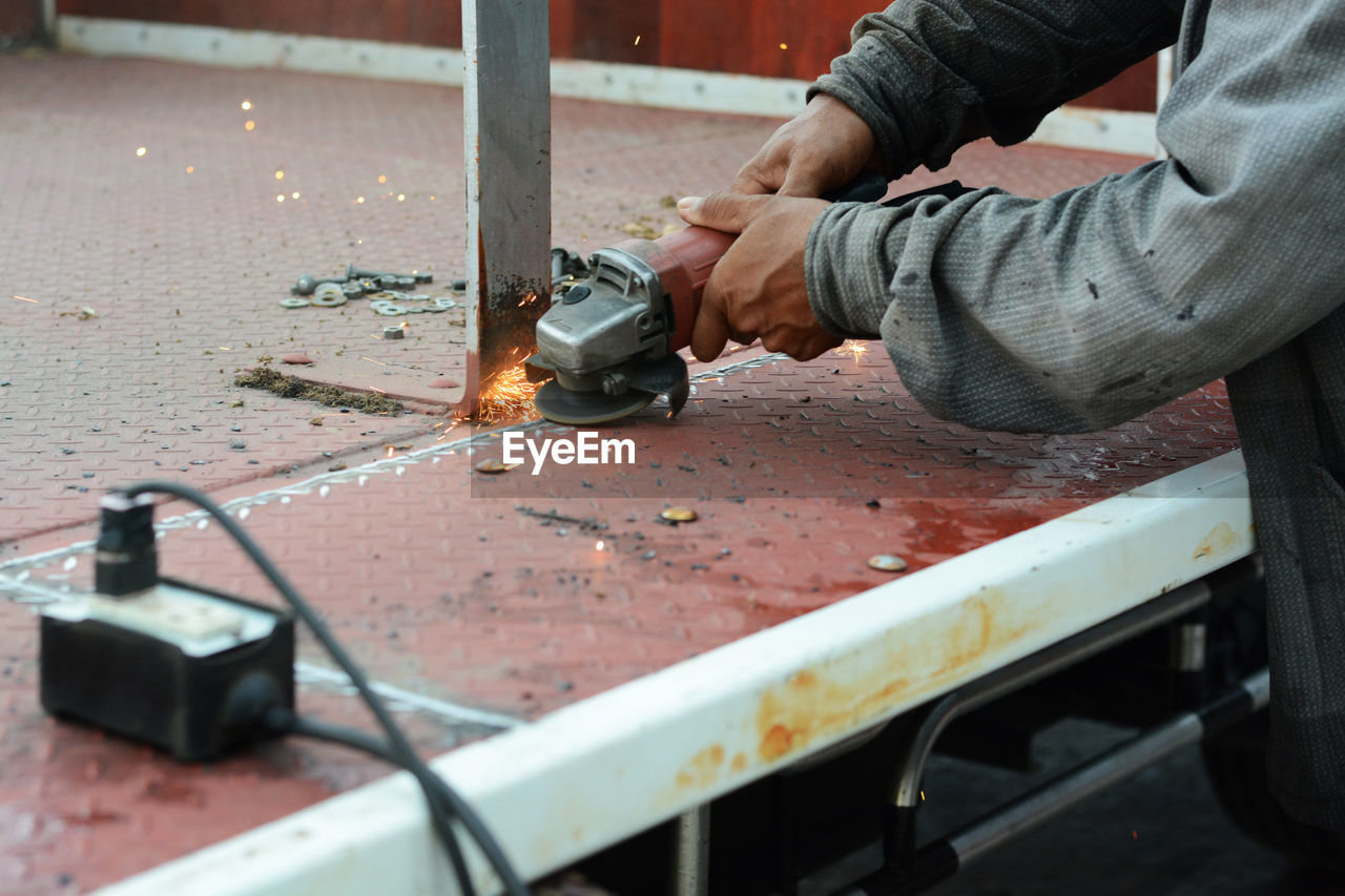 Midsection Of Worker Cutting Metal With Power Tool
