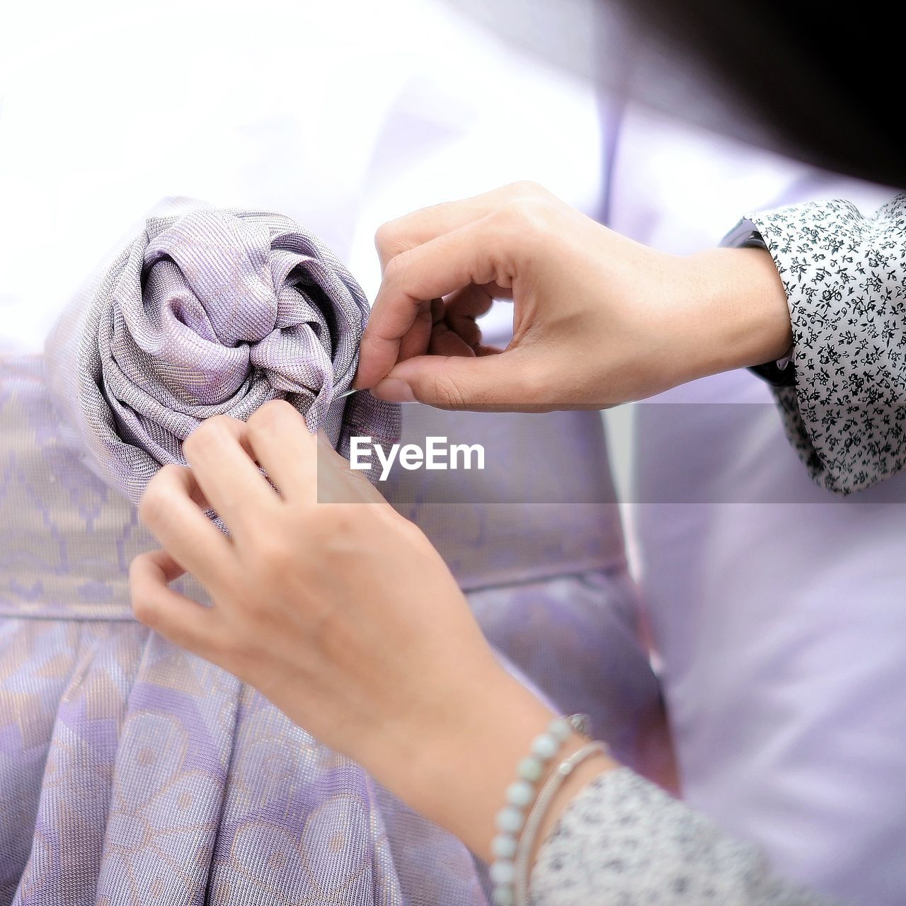 Cropped Hands Of Woman Sewing Ribbon Of Bride Dress