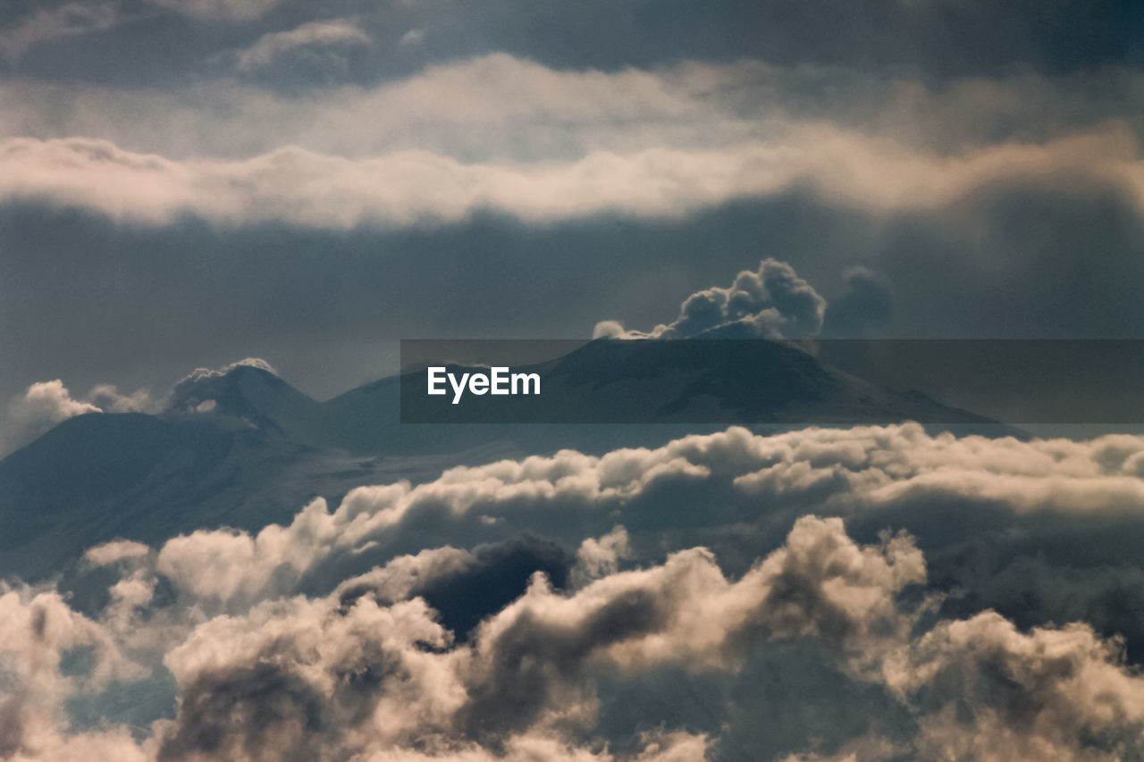Scenic view of snowcapped mountain against cloudy sky during sunset