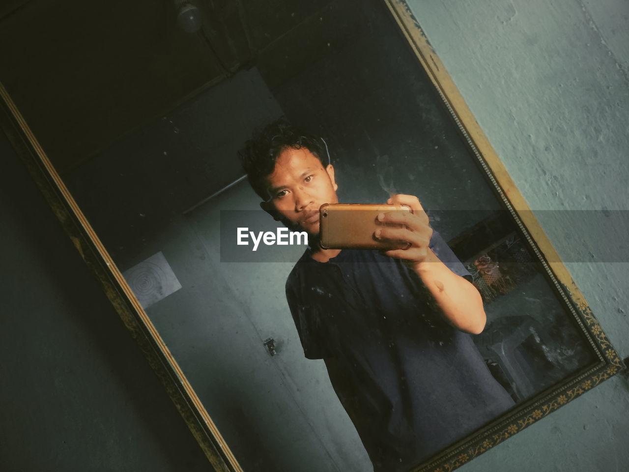 Portrait of man taking selfie in front of mirror
