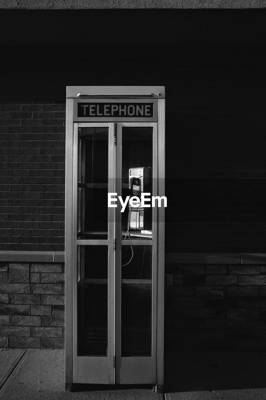 telephone, telephone booth, communication, pay phone, architecture, technology, building exterior, text, built structure, connection, western script, no people, day, outdoors, window, telecommunications equipment, transparent, glass - material, using phone