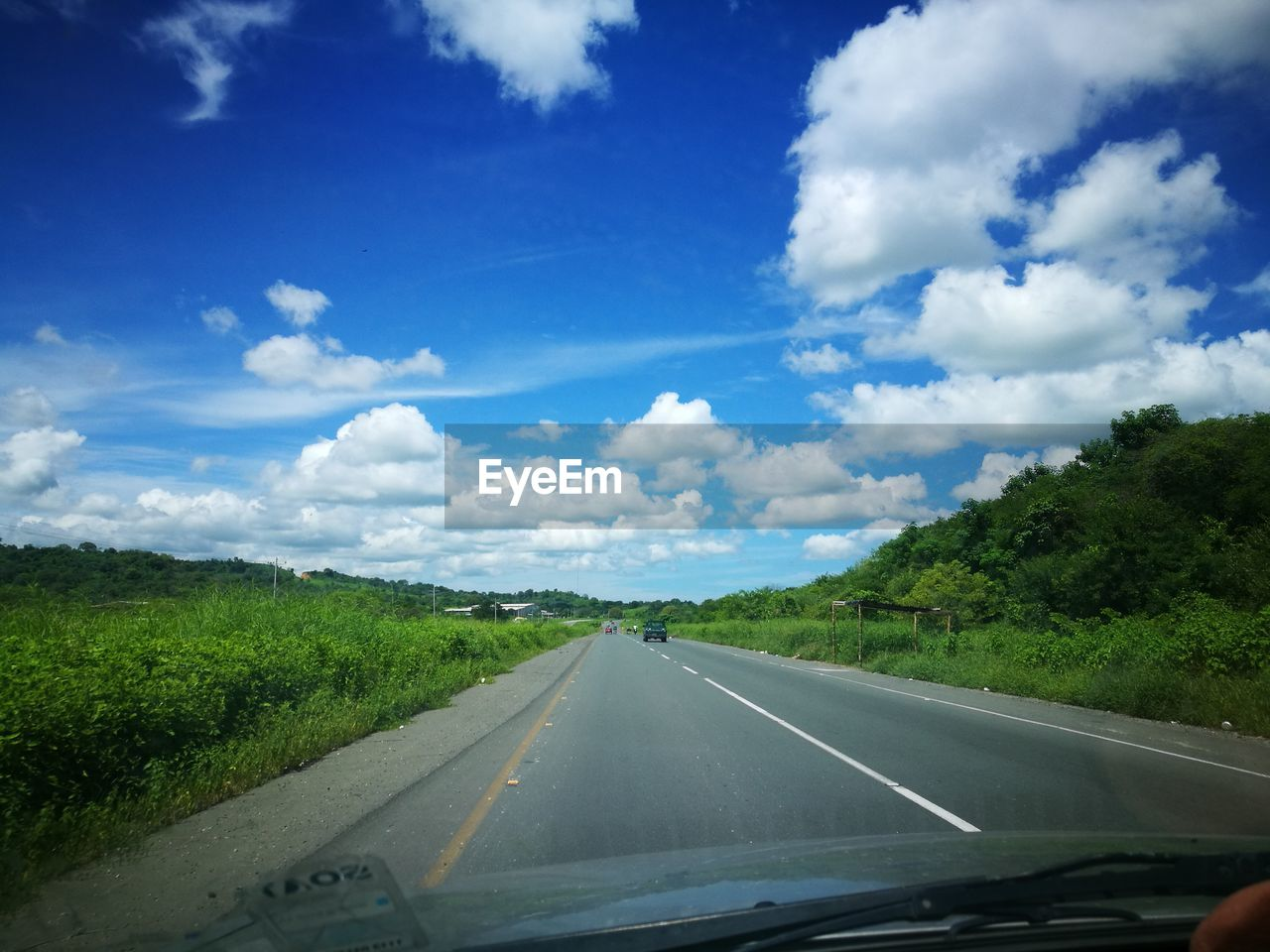 road, sky, transportation, cloud - sky, the way forward, car interior, windshield, day, nature, car, scenics, landscape, green color, no people, car point of view, tranquil scene, beauty in nature, land vehicle, mountain, tree, outdoors