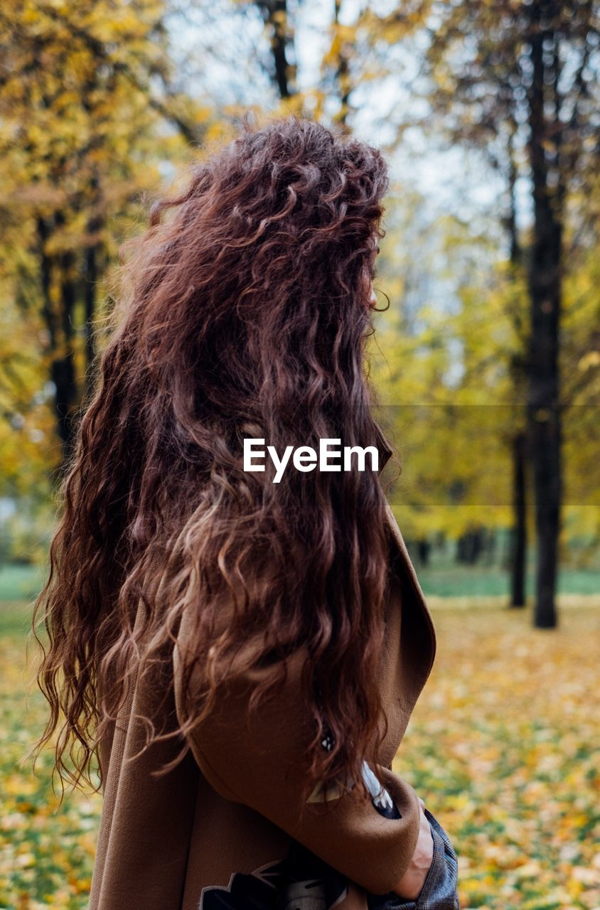 Side View Of Woman With Long Hair Standing At Park During Autumn