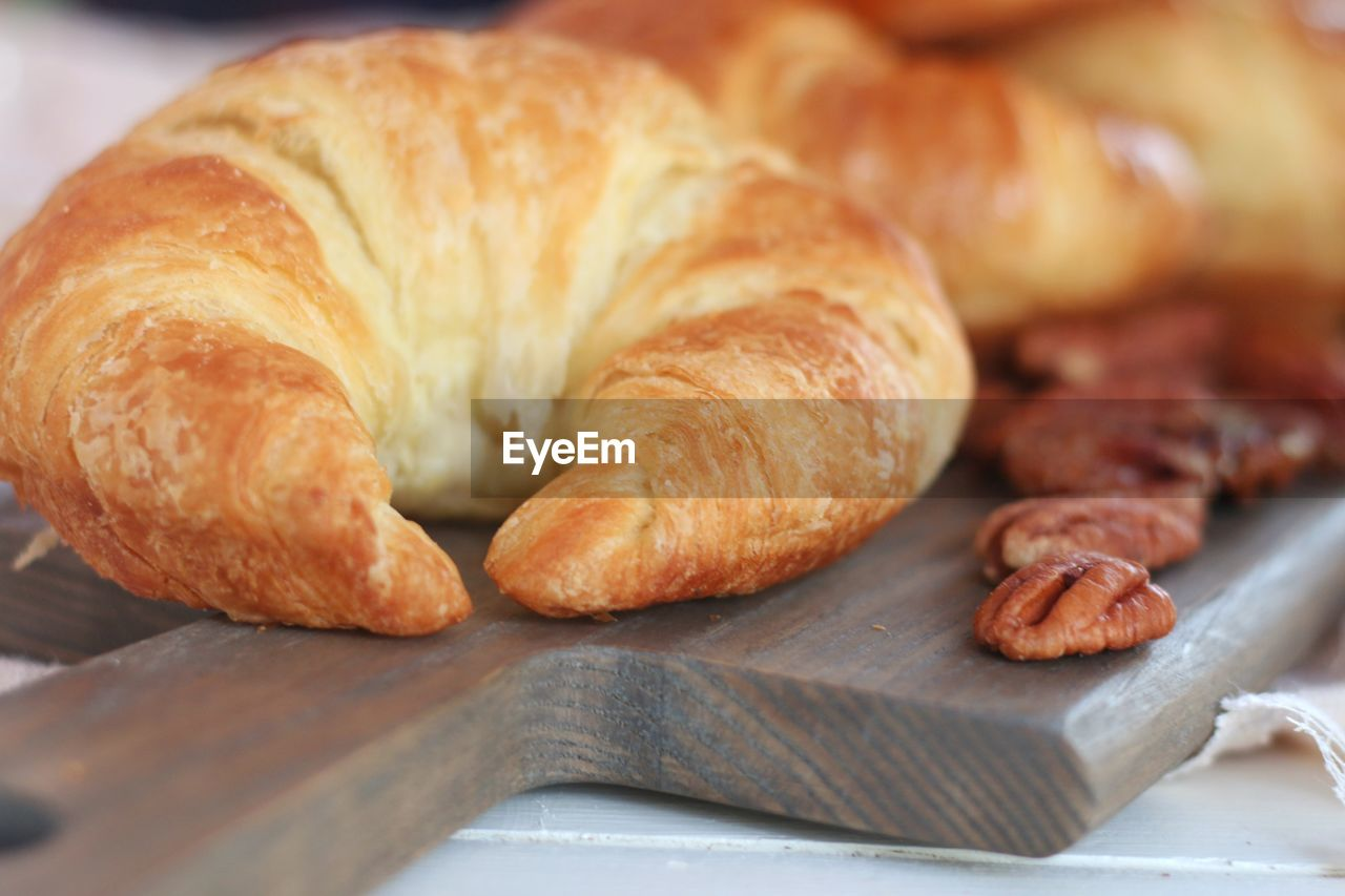 food, food and drink, baked, still life, freshness, croissant, close-up, french food, bread, indoors, no people, selective focus, ready-to-eat, brown, table, baked pastry item, cutting board, focus on foreground, sweet food, loaf of bread, breakfast, snack, tray, temptation