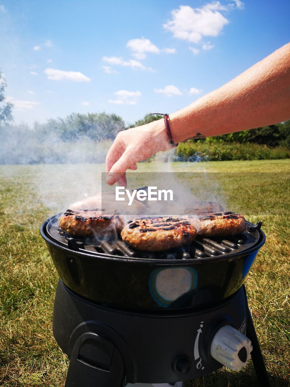 human hand, hand, human body part, one person, food and drink, barbecue, food, real people, land, day, holding, nature, smoke - physical structure, meat, heat - temperature, preparation, barbecue grill, sky, leisure activity, outdoors, preparing food, finger
