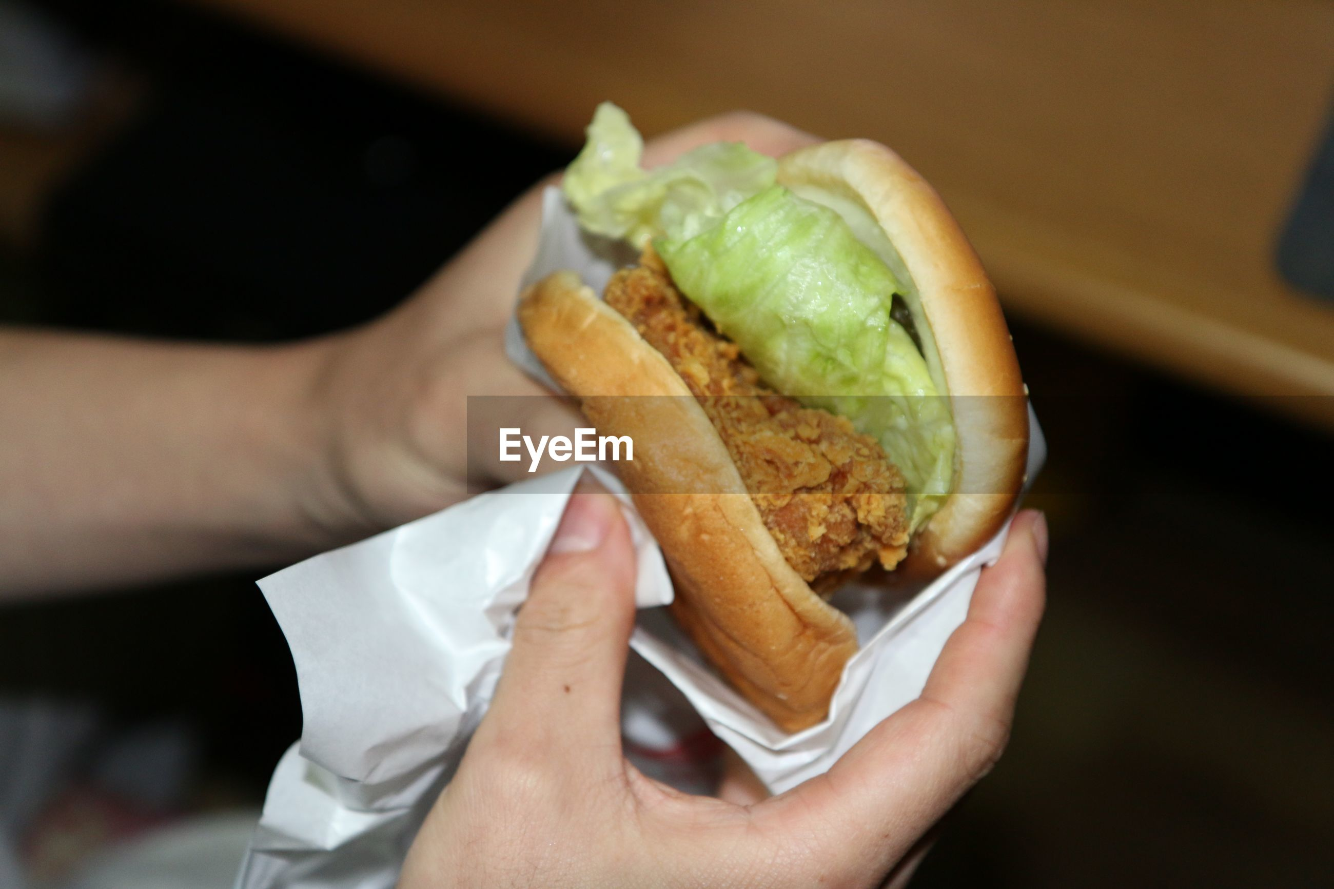 Cropped image of hand holding hamburger