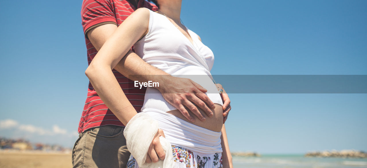 Midsection of man holding pregnant woman belly at beach