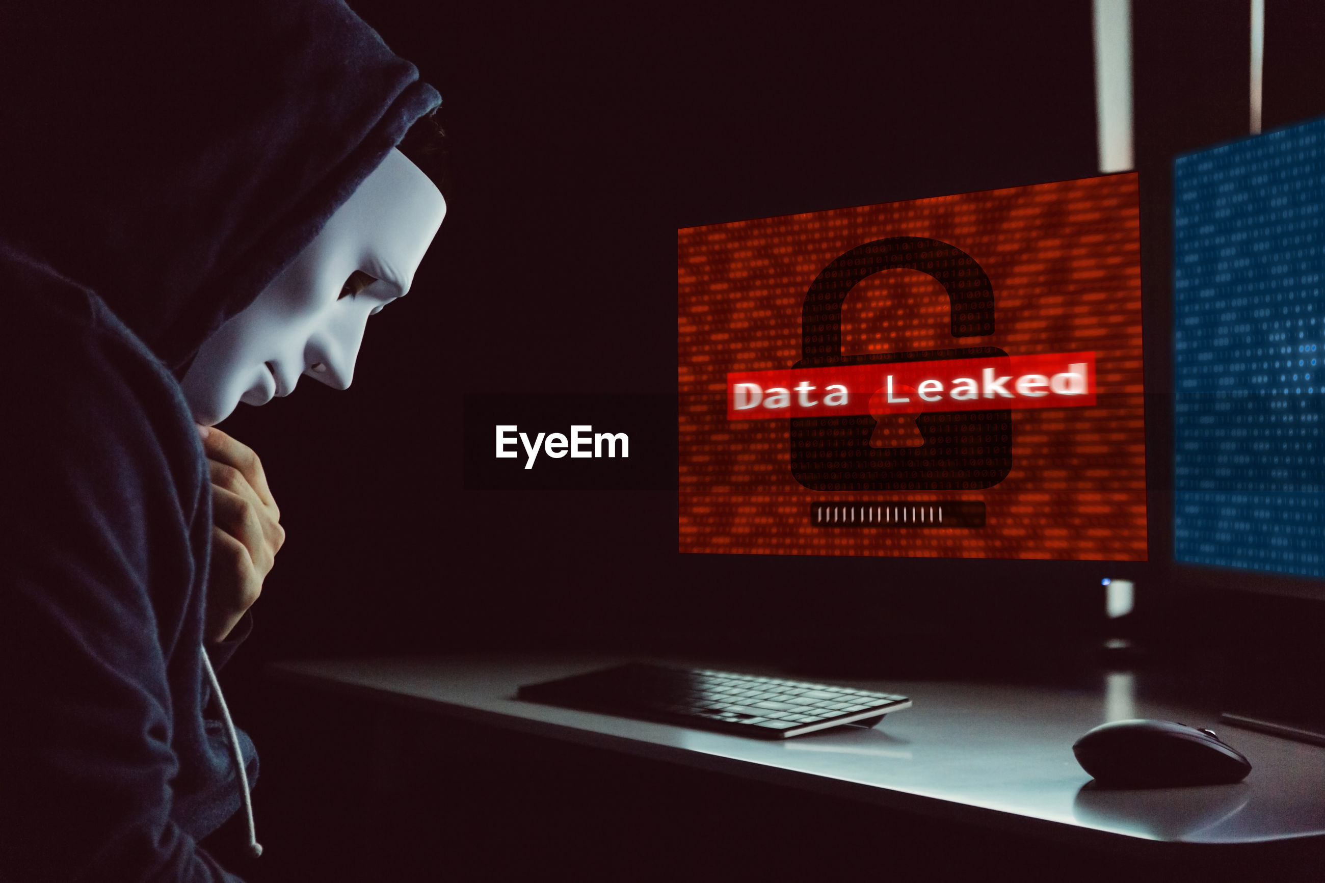 Side view of computer hacker wearing hooded shirt and mask by desktop pc