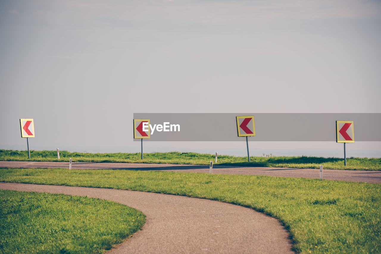 grass, environment, road, sky, flag, nature, plant, sign, field, no people, land, day, green color, copy space, communication, transportation, landscape, road sign, direction, outdoors, wind