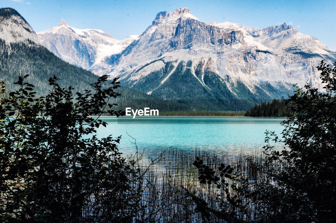 mountain, scenics - nature, beauty in nature, water, tranquil scene, lake, tranquility, tree, plant, sky, cold temperature, winter, idyllic, non-urban scene, nature, mountain range, snow, no people, snowcapped mountain, outdoors, mountain peak, turquoise colored