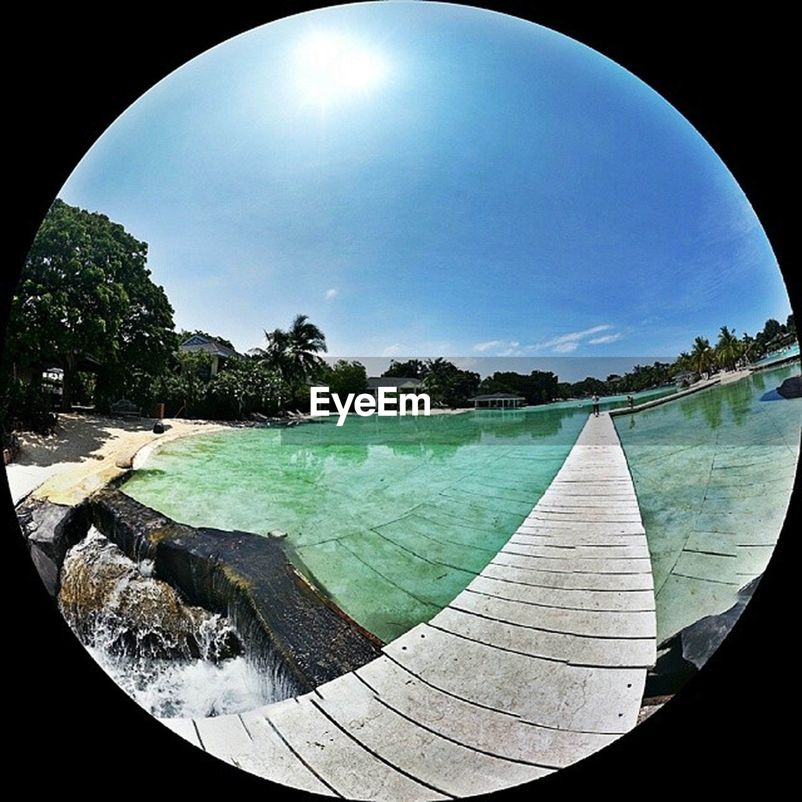 sky, fish-eye lens, cloud - sky, circle, water, blue, sunlight, cloud, reflection, tree, built structure, tranquility, nature, day, panoramic, arch, outdoors, beauty in nature, no people, tranquil scene