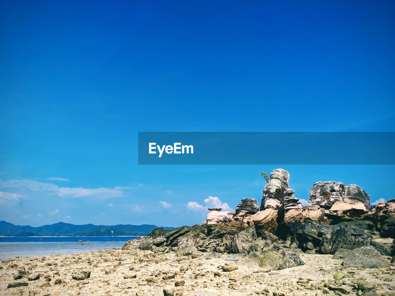 sky, blue, rock, scenics - nature, beauty in nature, rock - object, solid, tranquil scene, tranquility, nature, copy space, day, rock formation, sea, land, no people, non-urban scene, sunlight, idyllic, water, outdoors, arid climate, eroded