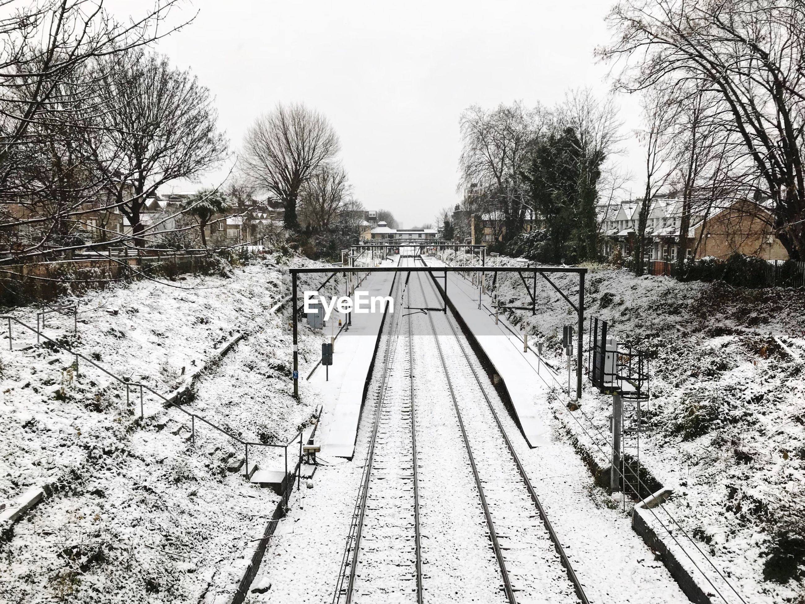 SNOW COVERED RAILROAD TRACKS AGAINST SKY