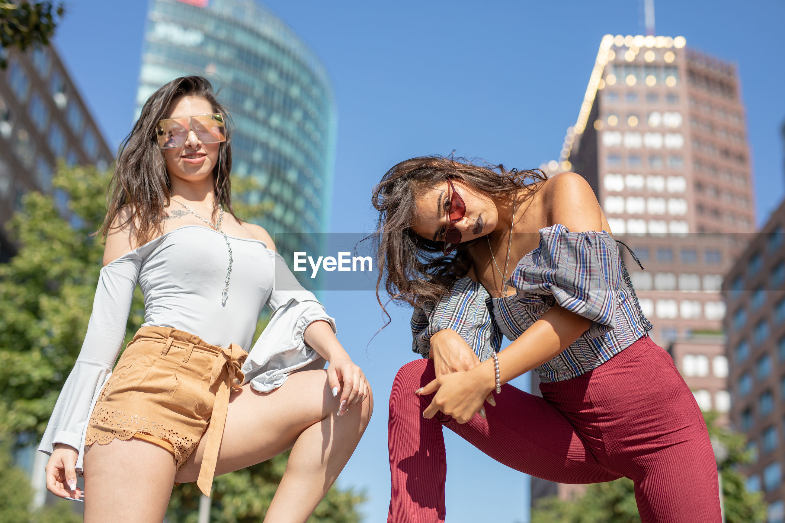 Portrait of young women standing against buildings and sky