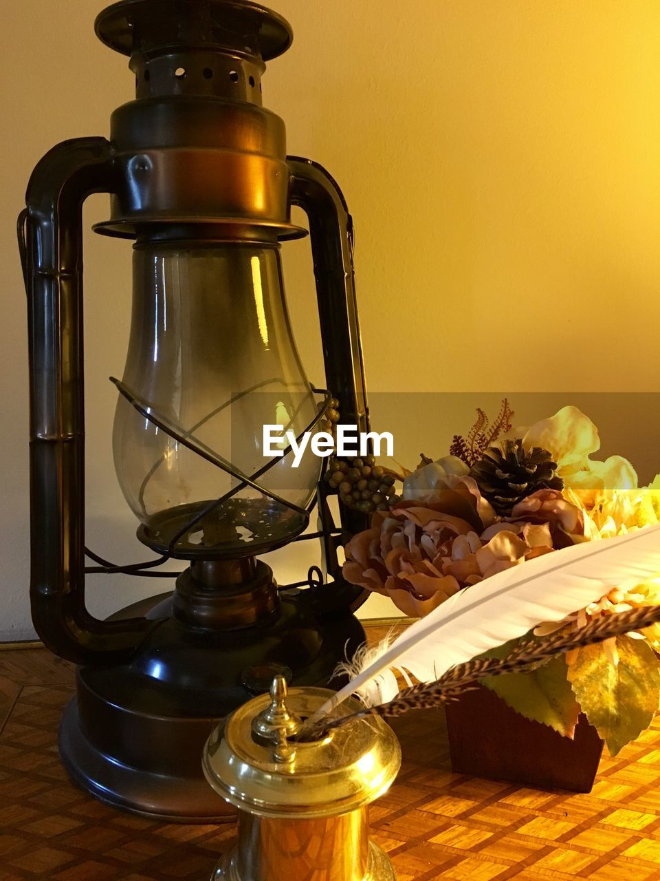 Old-fashioned lantern by artificial flowers on table