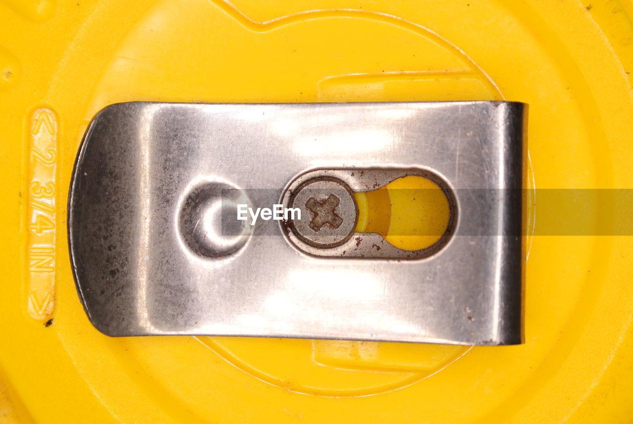 Close-Up Of Metallic Clip On Yellow Equipment