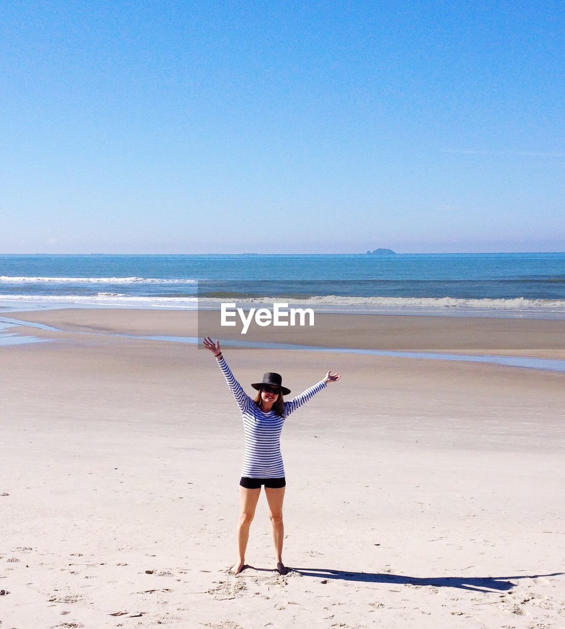 Young woman with arms raised standing at beach against sky