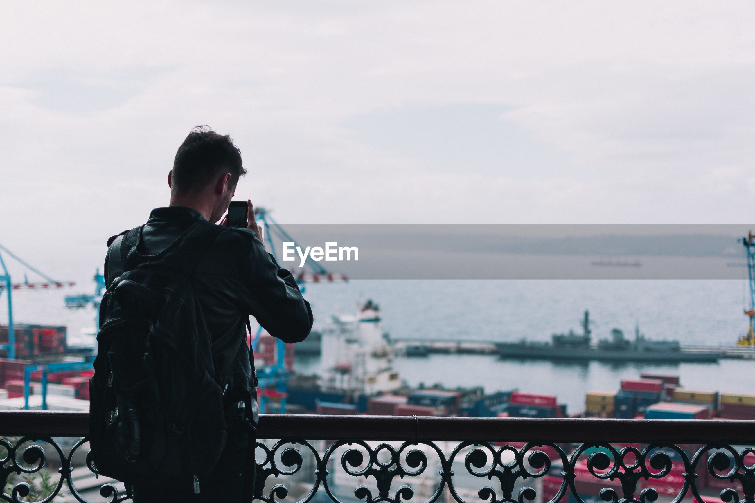 Rear view of man photographing against sea