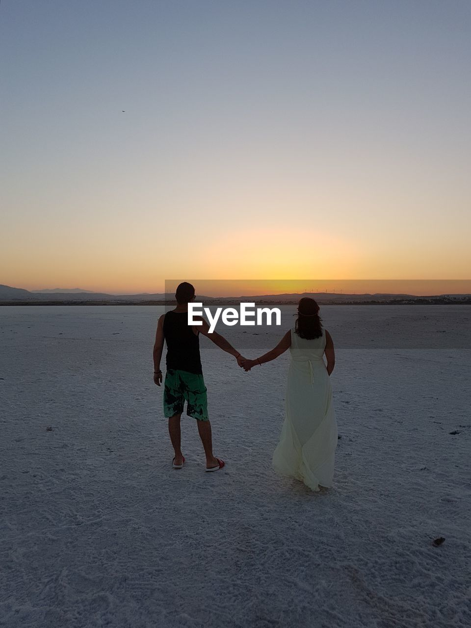 Rear view of couple holding hands walking at beach against sky during sunset