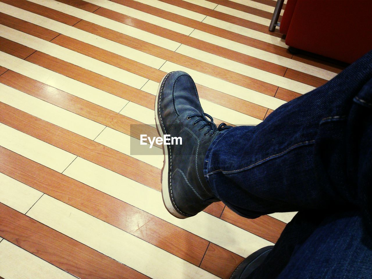 Low section of man sitting against tiled floor