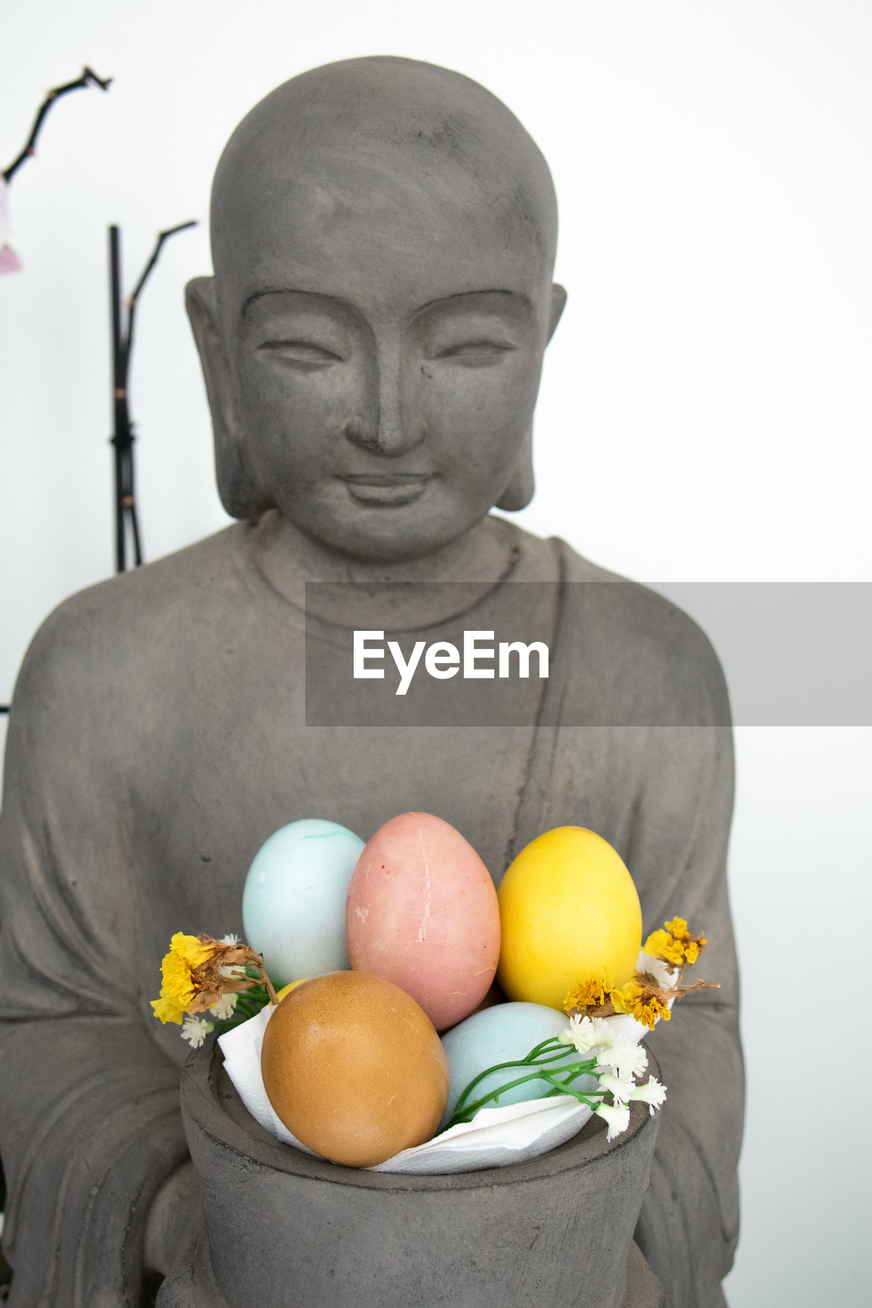 Buddhist statue holding a basket of easter eggs painted with eco products
