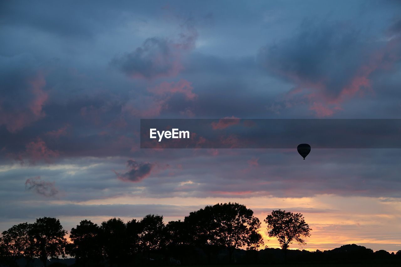 sunset, sky, cloud - sky, tree, silhouette, nature, beauty in nature, scenics, dramatic sky, tranquil scene, tranquility, low angle view, outdoors, mid-air, no people, hot air balloon, day