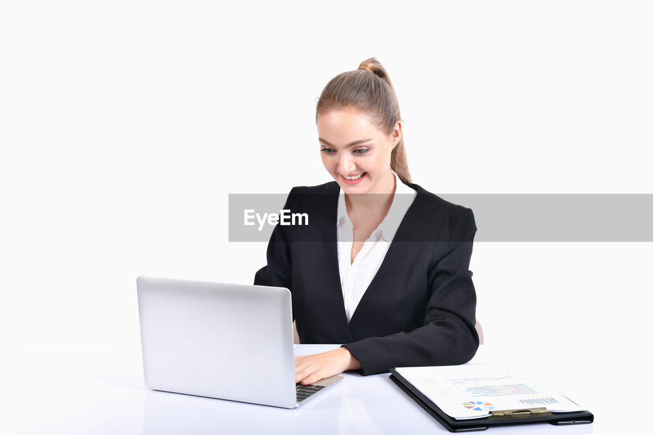 smiling, wireless technology, young adult, laptop, businesswoman, business, young women, women, computer, white background, front view, communication, business person, one person, occupation, technology, indoors, happiness, using laptop, office, beautiful woman