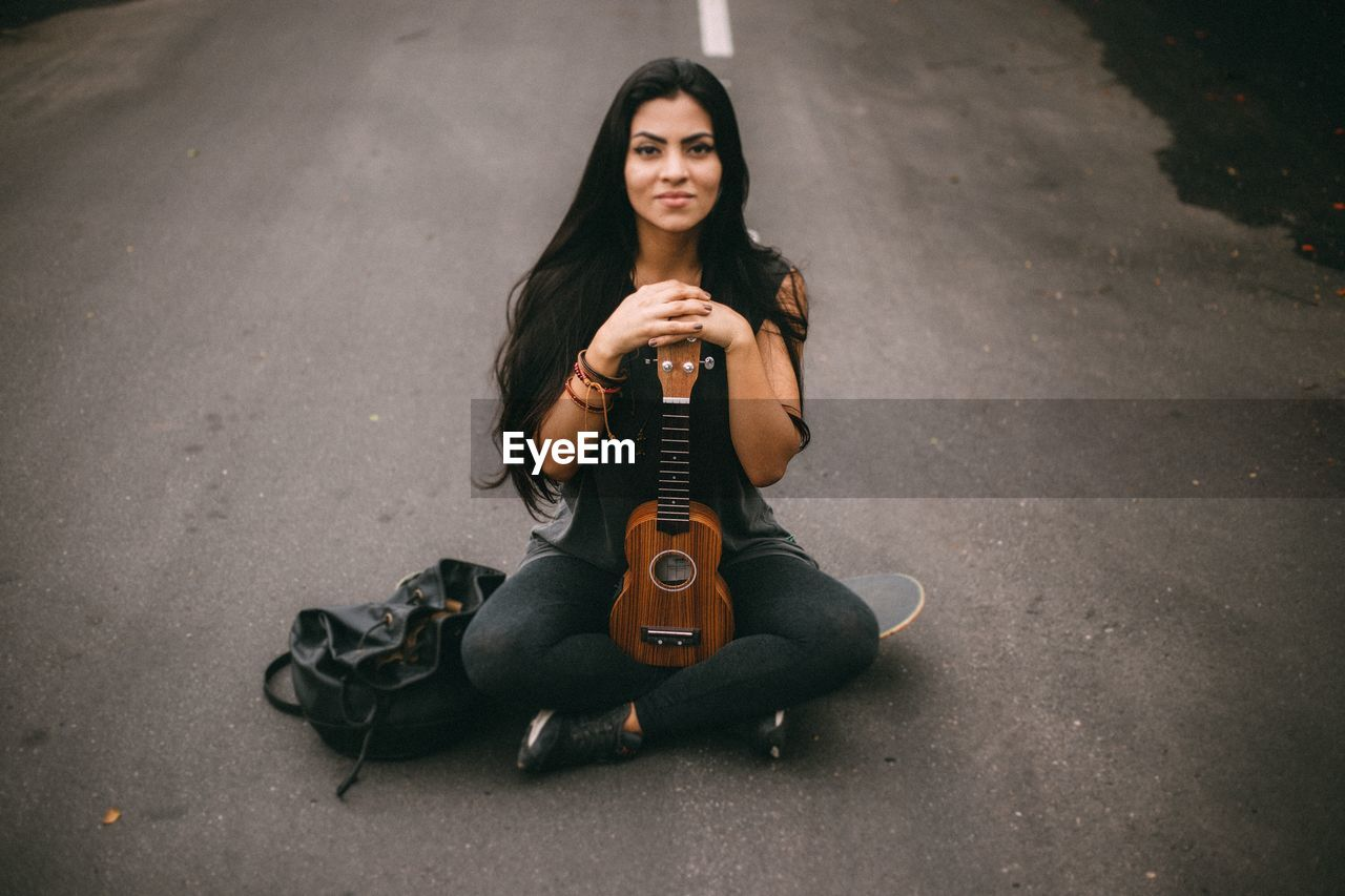 music, one person, looking at camera, portrait, front view, musical instrument, arts culture and entertainment, young adult, leisure activity, string instrument, casual clothing, real people, musical equipment, playing, lifestyles, guitar, full length, young women, sitting, musician, outdoors, acoustic guitar, beautiful woman