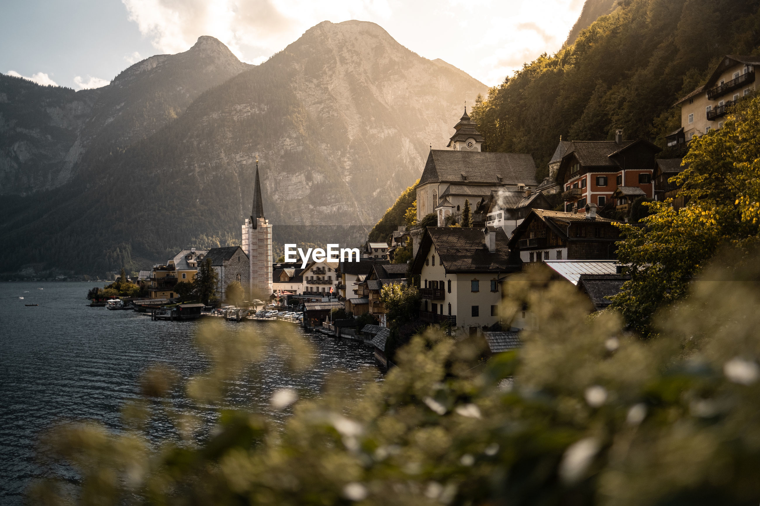 Buildings and mountains by lake in city