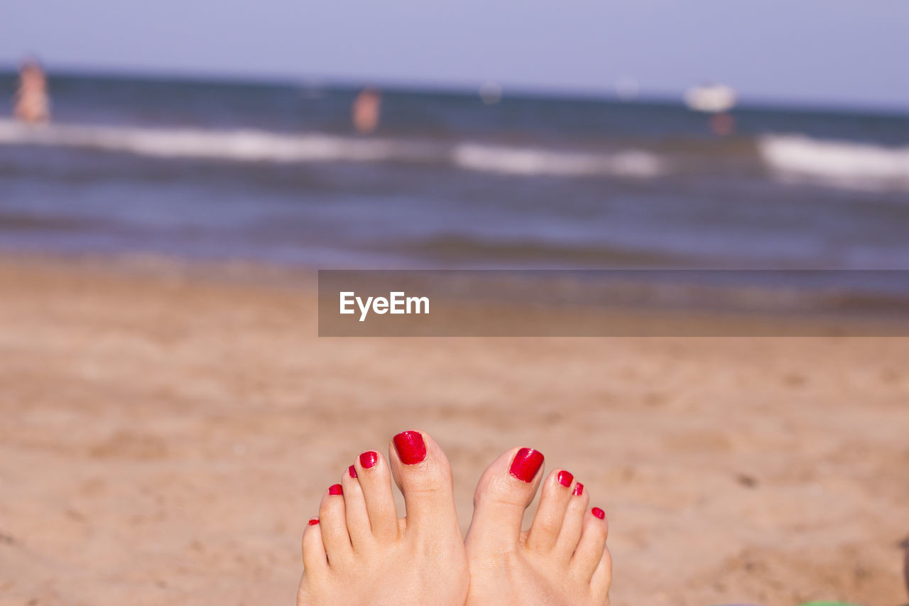 Low section of woman with red nail polish at beach