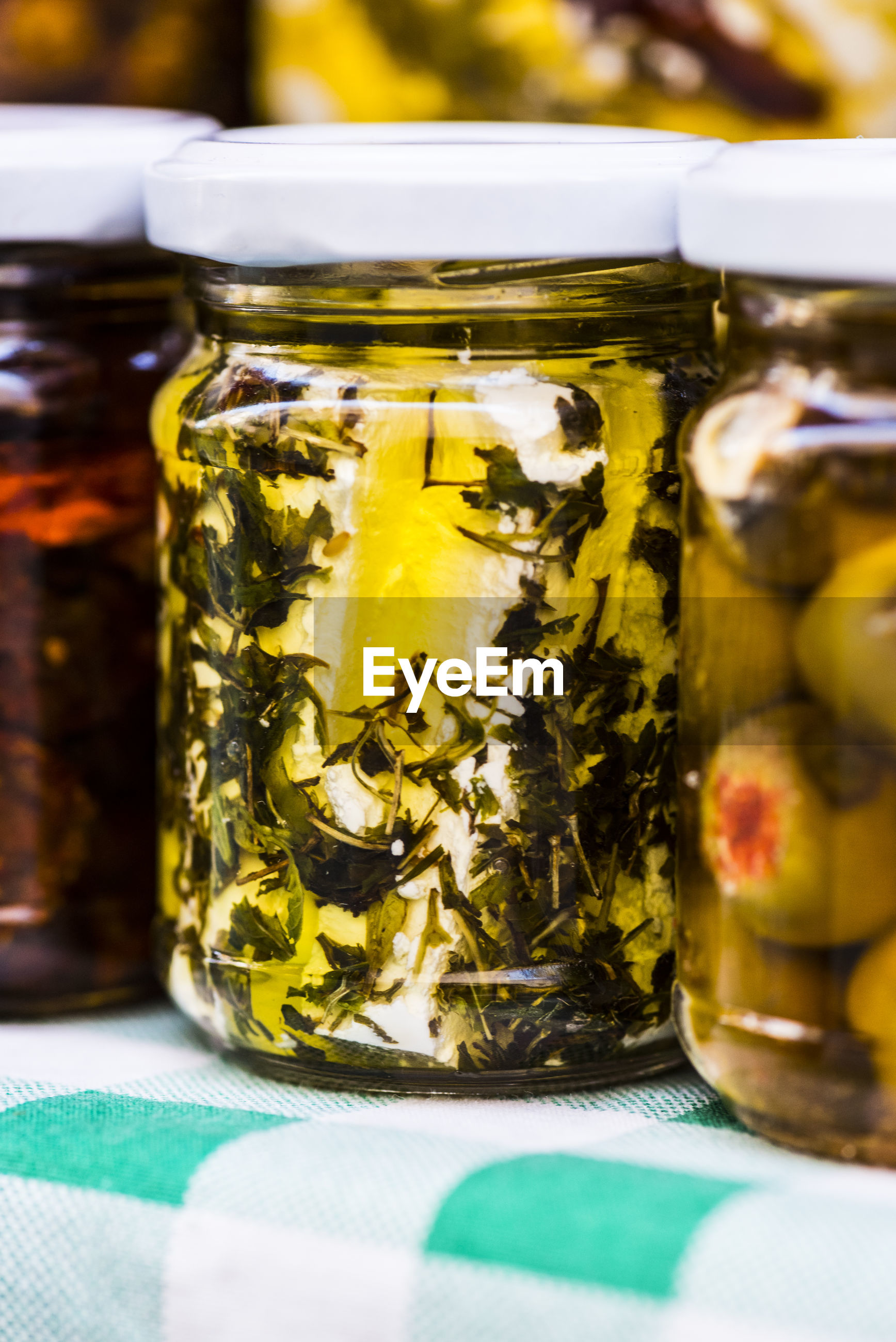 Close-up of pickles in glass jars on table