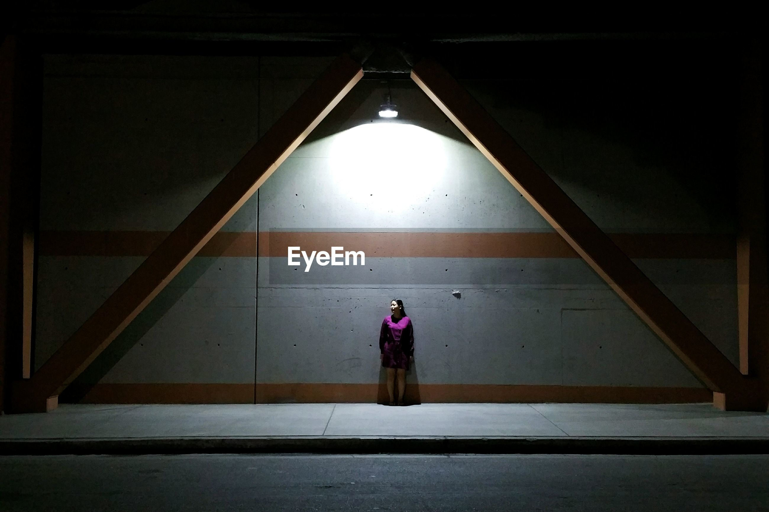 Full length of woman standing against wall on sidewalk in city at night