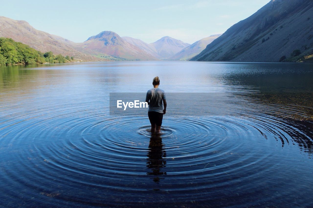 Scenic Rear View Of Young Woman Walking In Lake