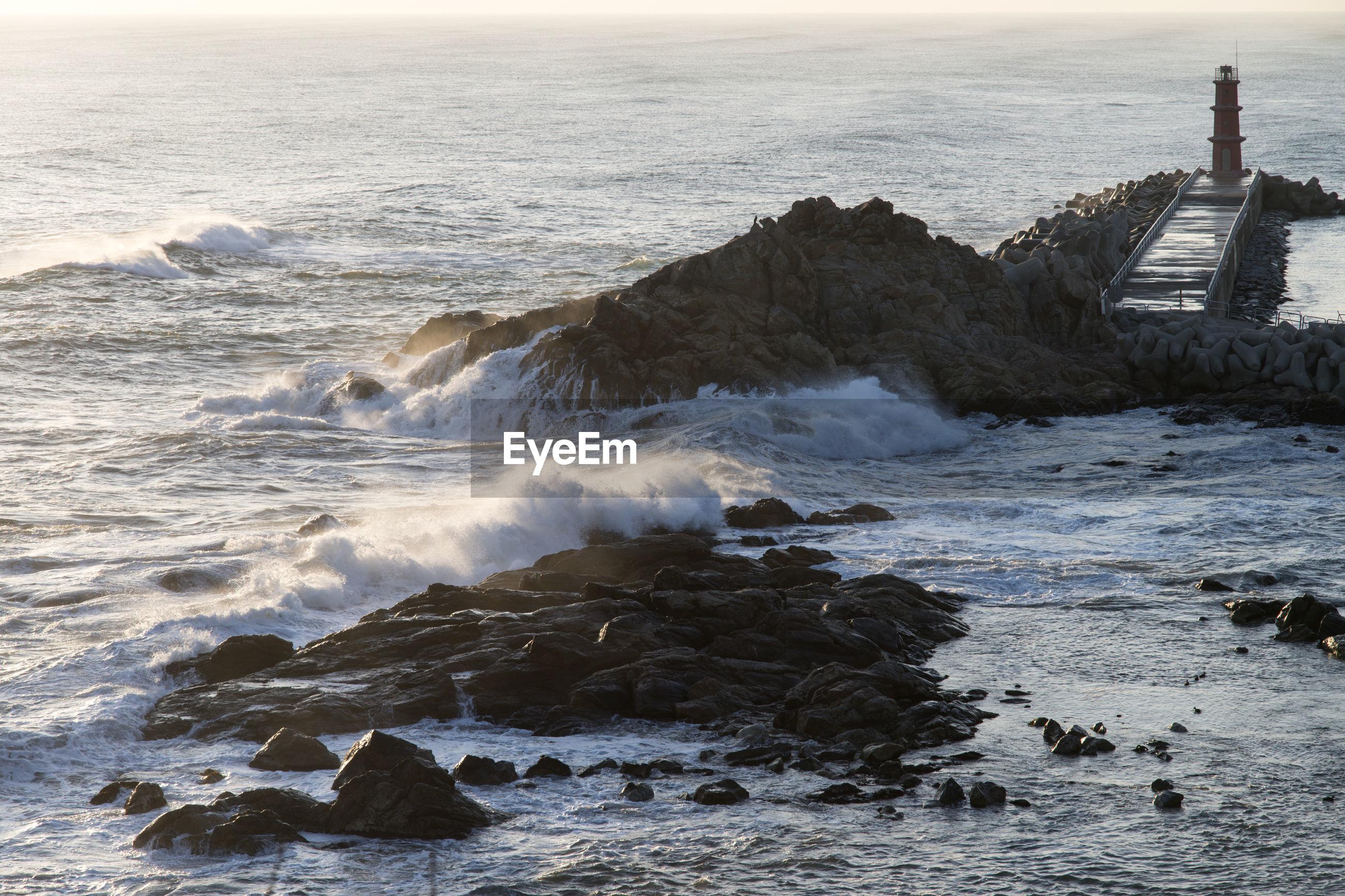 Wave splashing rocks in sea