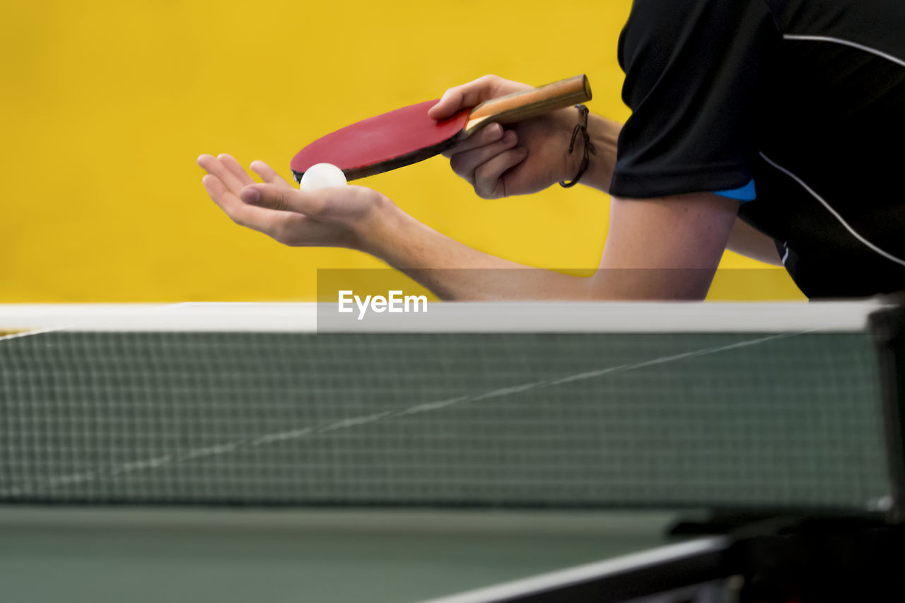 real people, midsection, one person, human hand, playing, human body part, holding, men, hand, sport, indoors, lifestyles, table tennis, yellow, focus on foreground, publication, selective focus, book, leisure activity, finger