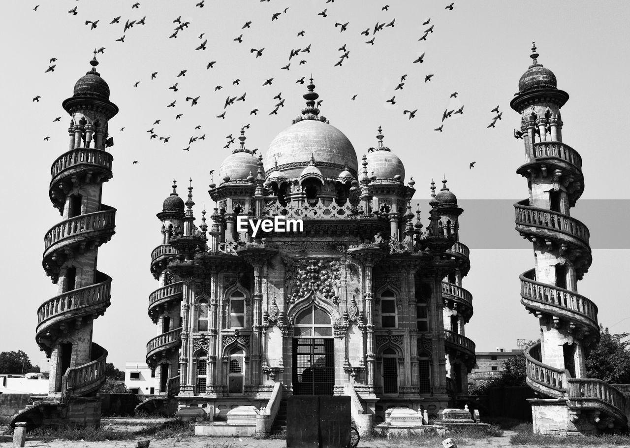 Flock Of Birds Flying Over Mahabat Maqbara Against Sky