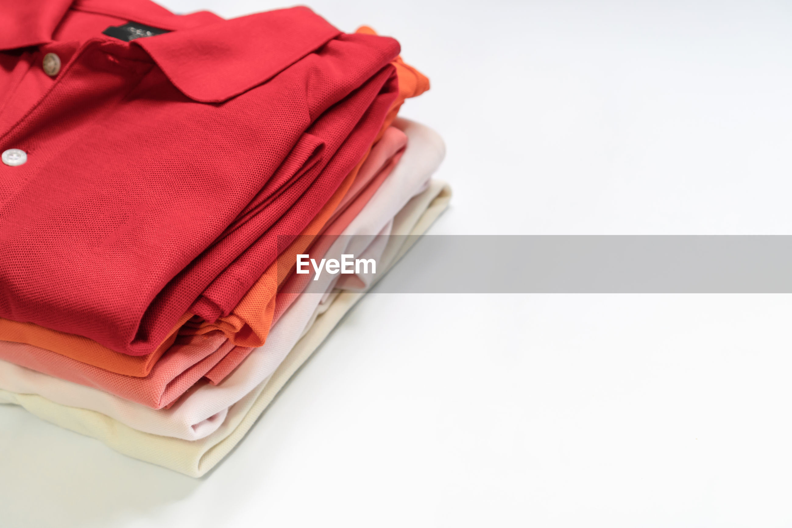 High angle view of folded t-shirts on white background