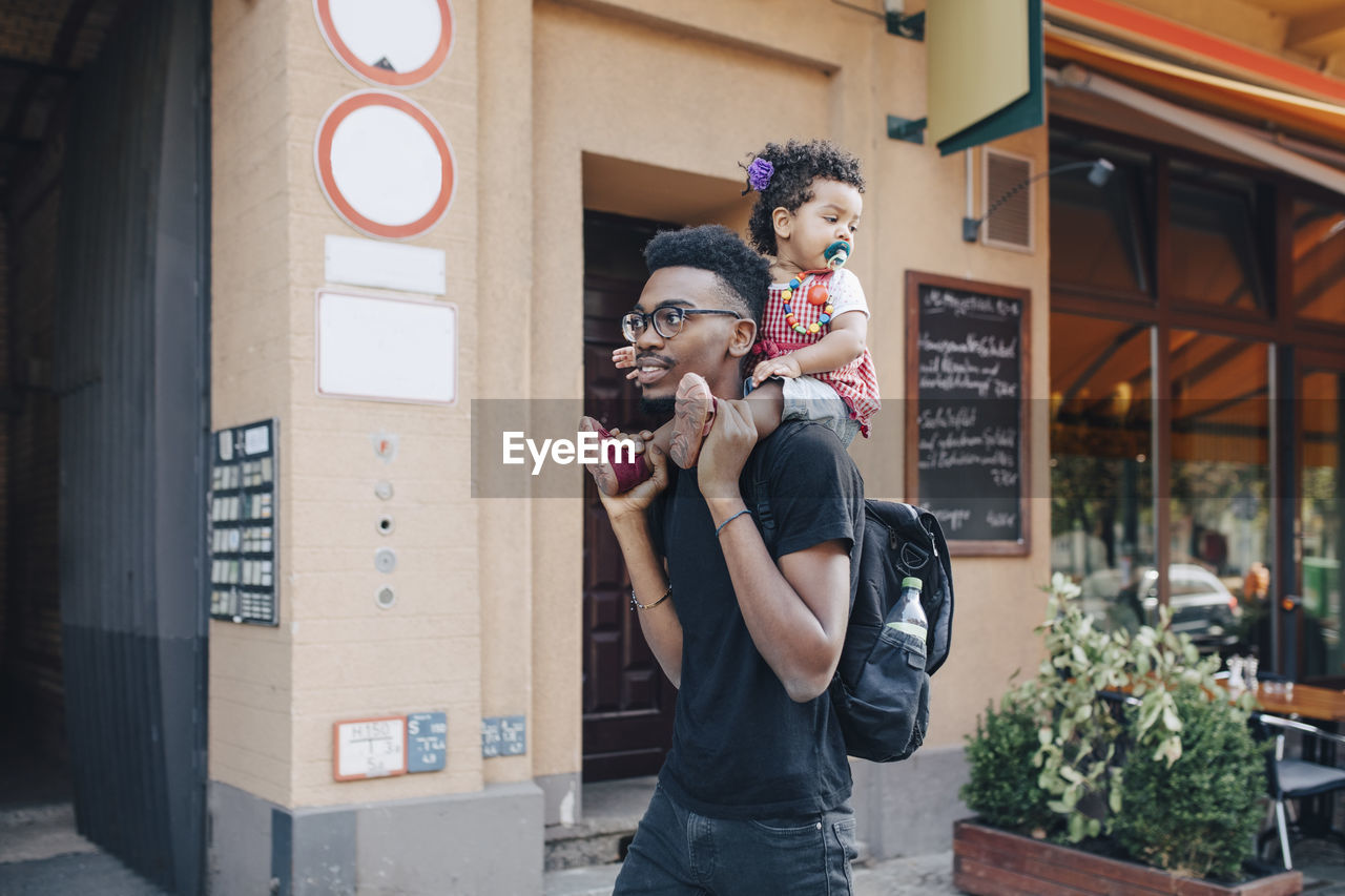 Young man carrying daughter on shoulders while walking by building