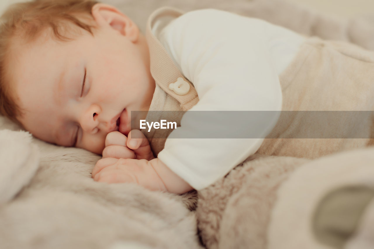 childhood, child, baby, lying down, innocence, young, eyes closed, one person, relaxation, babyhood, real people, sleeping, indoors, furniture, bed, cute, selective focus, resting, comfortable, newborn