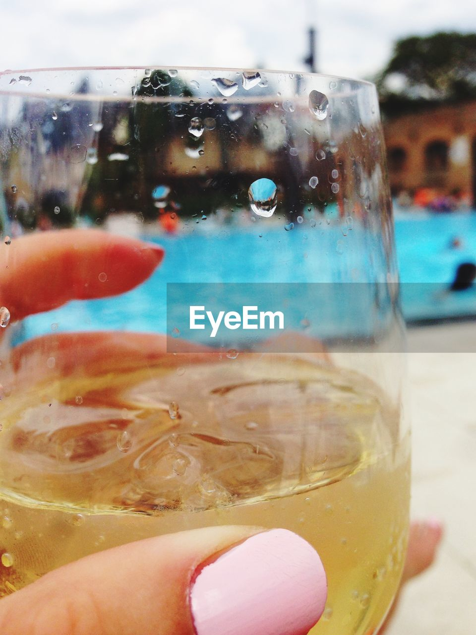 Cropped image of woman hand holding wineglass by swimming