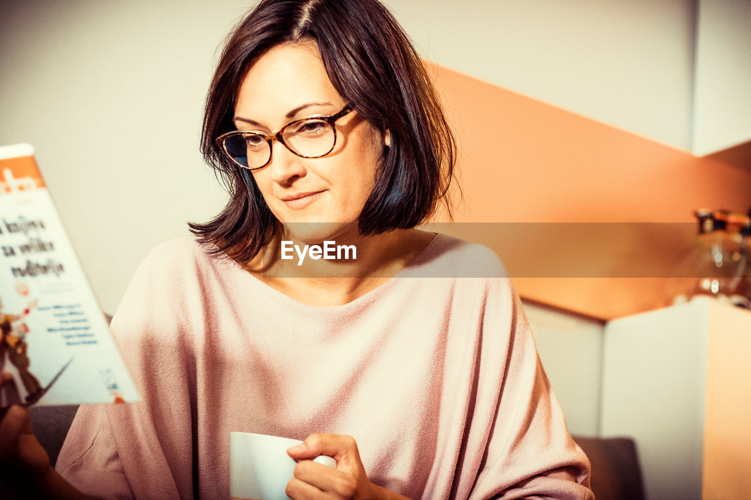 Smiling woman reading a novel while relaxing at home and drinking coffee.