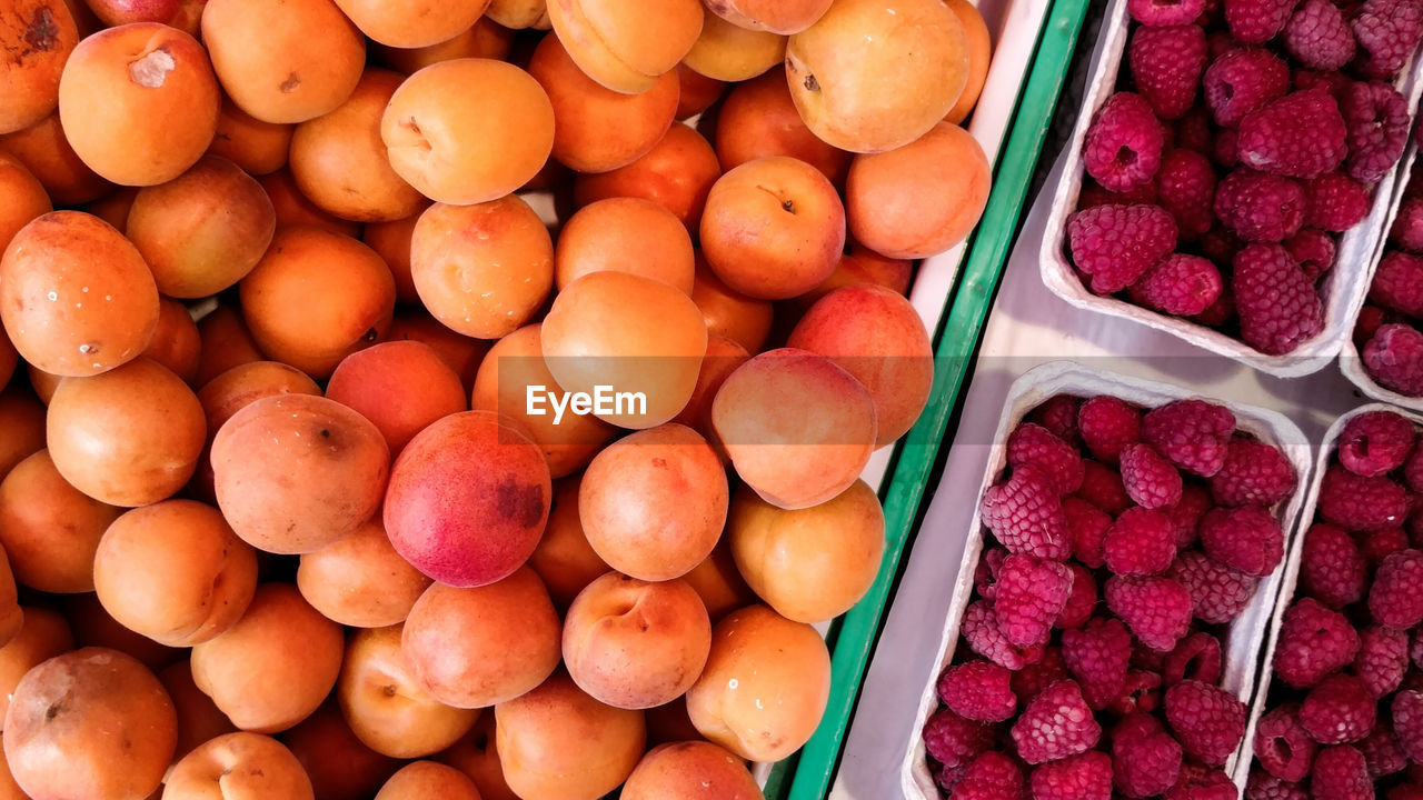 Directly Above Shot Of Peaches And Raspberries For Sale At Market Stall