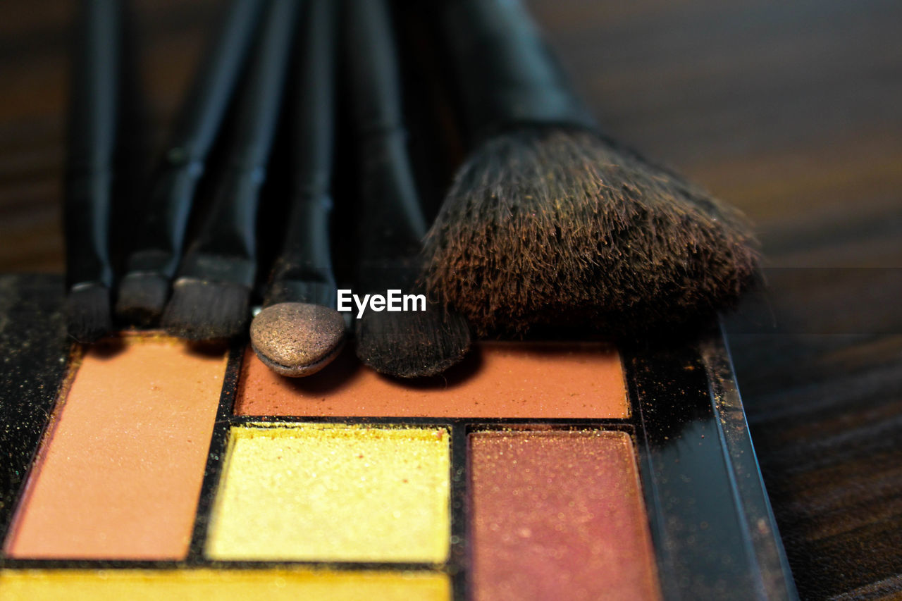 Close-Up Of Face Powder And Make-Up Brushes On Table