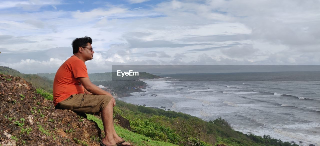one person, water, sea, scenics - nature, sky, sitting, young men, leisure activity, young adult, beauty in nature, side view, full length, real people, casual clothing, nature, non-urban scene, land, horizon, horizon over water, looking at view, outdoors, contemplation