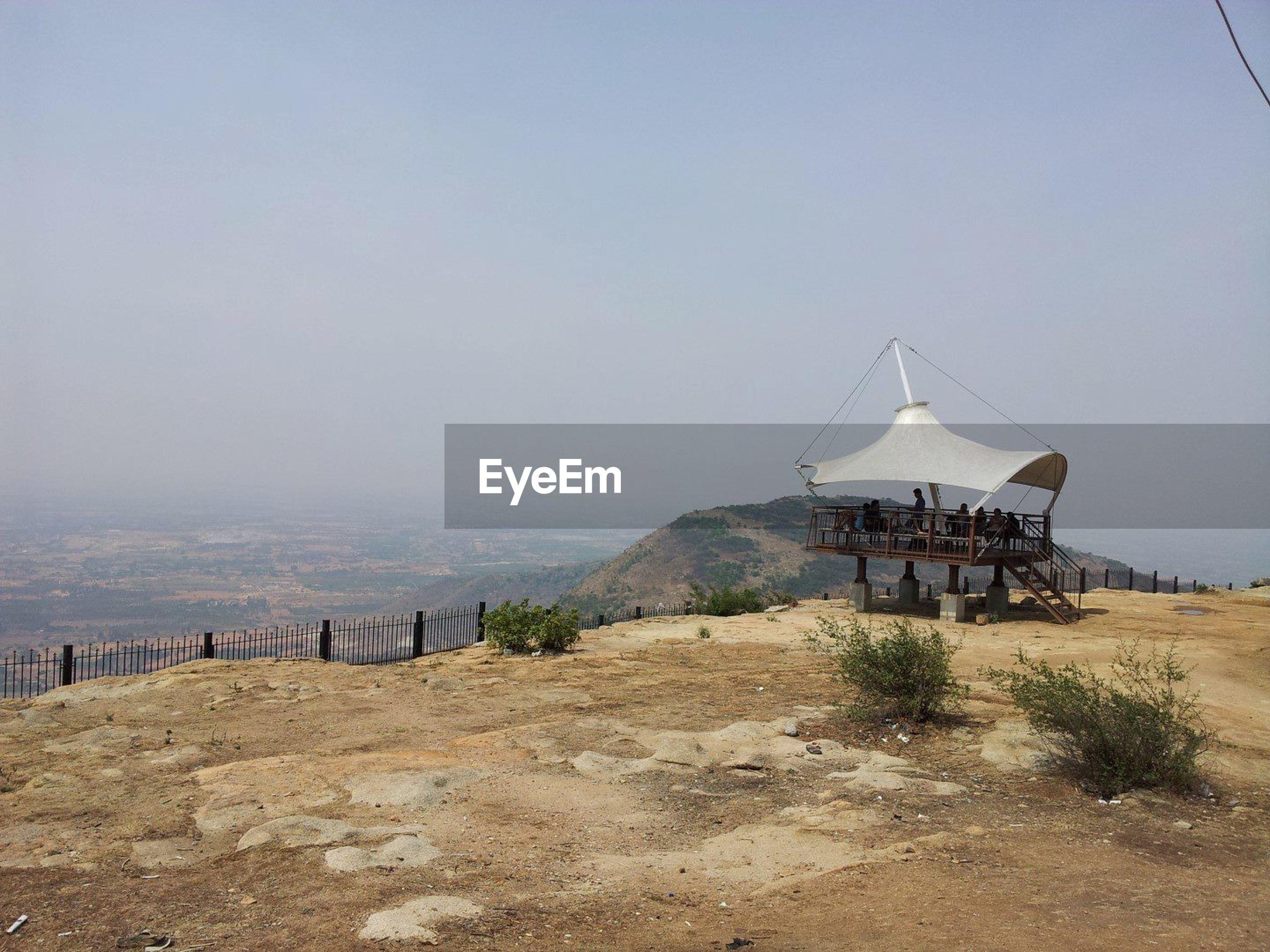 People in gazebo on mountain against sky