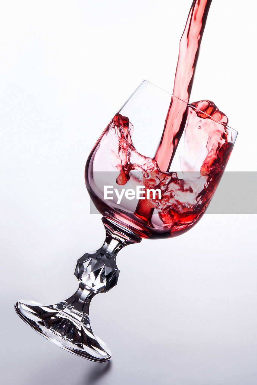 white background, studio shot, indoors, refreshment, glass, no people, drink, alcohol, red, close-up, wineglass, food and drink, copy space, still life, motion, glass - material, splashing, pouring, transparent, red wine, high-speed photography