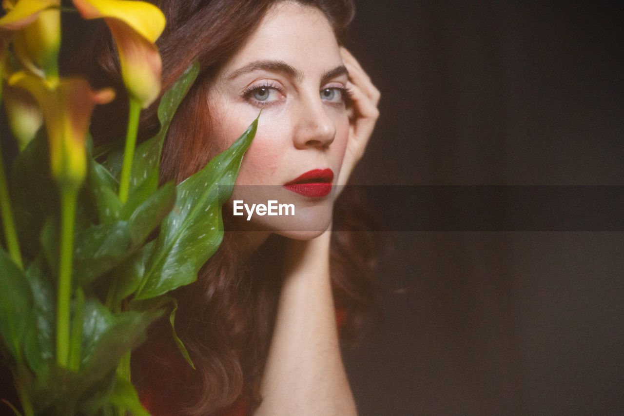 Close-up portrait of beautiful woman by plants