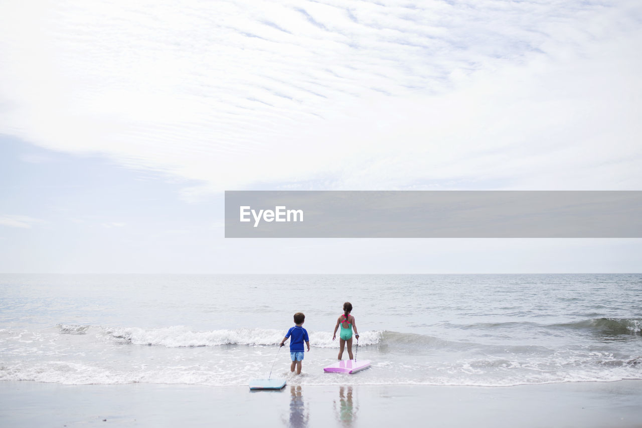Scenic View Of Children Wading Into Sea Against Sky