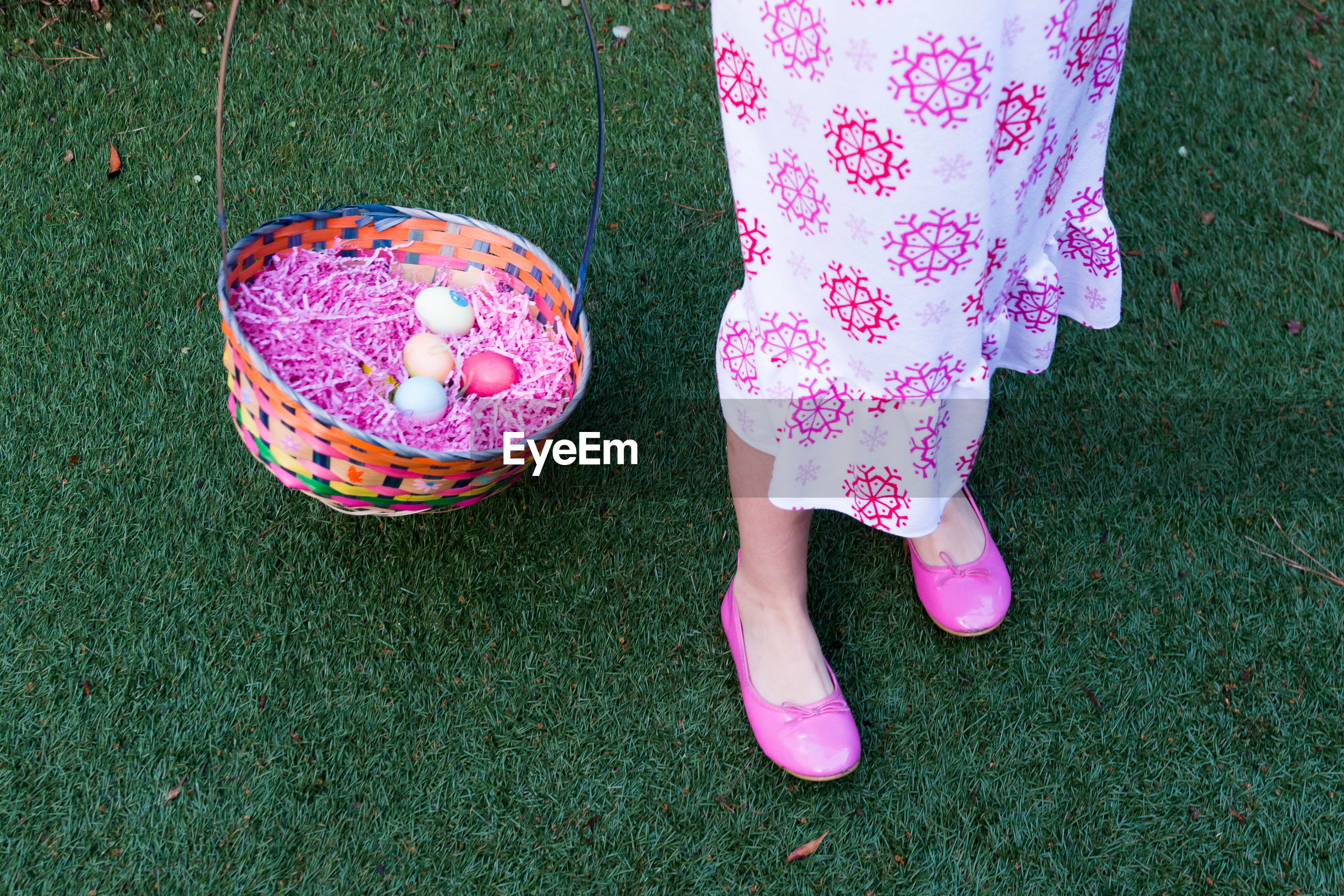 Low section of woman with easter basket on grassy field